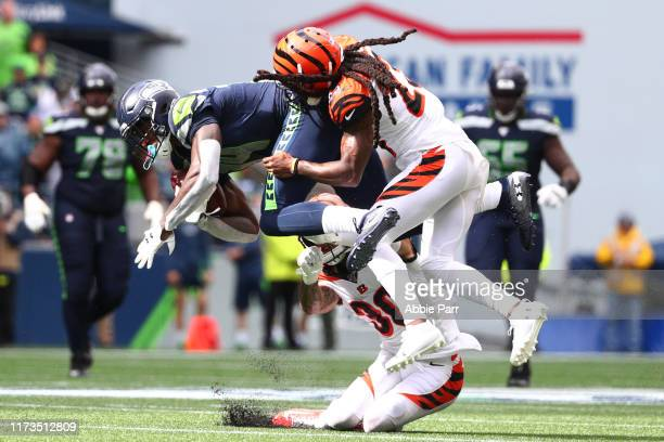 K Metcalf of the Seattle Seahawks completes a pass against Jessie Bates and BW Webb of the Cincinnati Bengals in the third quarter during their game...