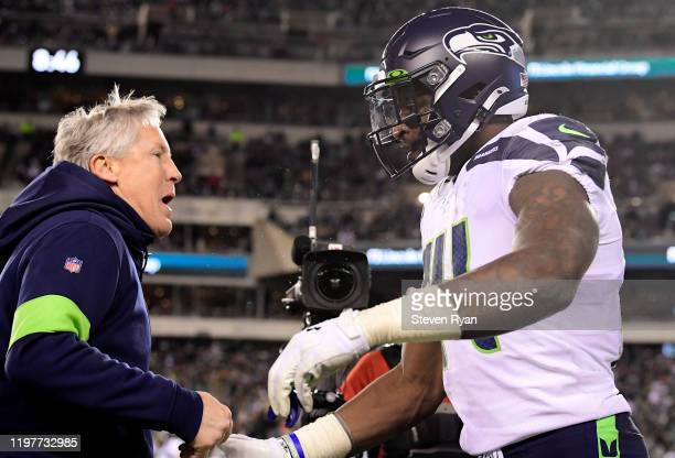 K Metcalf of the Seattle Seahawks is congratulated by head coach Pete Carroll after his touchdown in the third quarter of the NFC Wild Card Playoff...