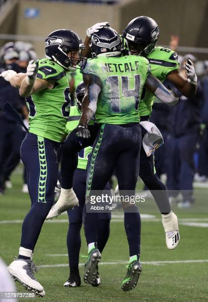Metcalf of the Seattle Seahawks is congratulated by teammates after scoring the game winning touchdown against the Minnesota Vikings during the...