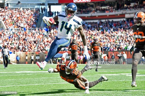 K Metcalf of the Seattle Seahawks leaps over Damarious Randall of the Cleveland Browns or extra yards during the second quarter at FirstEnergy...