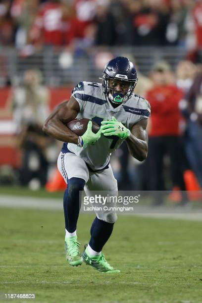 K Metcalf of the Seattle Seahawks runs with the ball after making a catch in overtime against the San Francisco 49ers at Levi's Stadium on November...