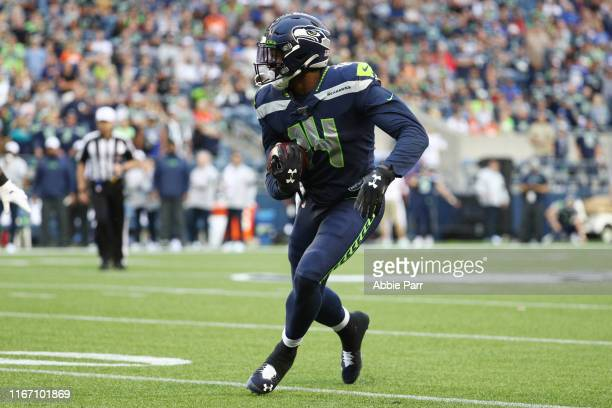 K Metcalf of the Seattle Seahawks runs with the ball against the Denver Broncos in the fourth quarter during their preseason game at CenturyLink...