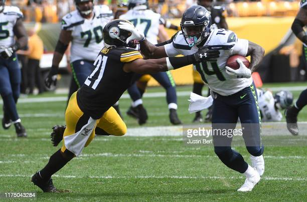 K Metcalf of the Seattle Seahawks stiff arms Sean Davis of the Pittsburgh Steelers after a reception in the third quarter during the game at Heinz...