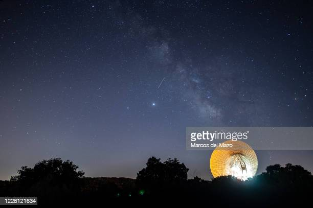 Meteor crossing the night sky over the Milky way and a large antenna of the Madrid Deep Space Communications Complex of NASA and JPL, used for for...