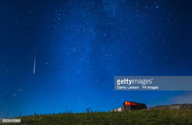 A meteor during the Perseid meteor shower seen from near Hawes in the Yorkshire Dales National Park as the Earth flies through a cloud of cometary...