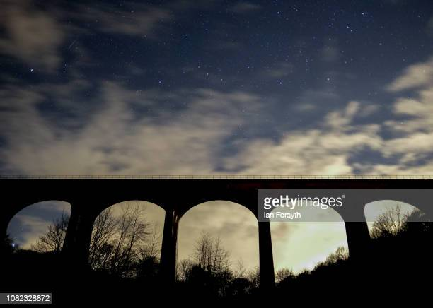 A meteor from the Geminid Meteor shower streaks across the night sky above a railway viaduct on December 14 2018 in Saltburn By The Sea United...