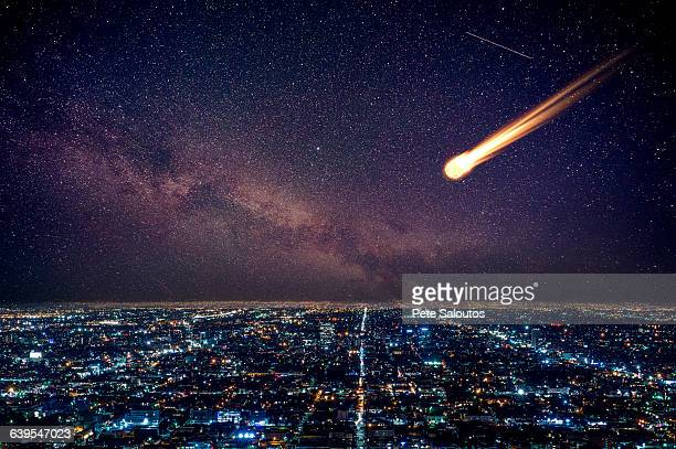 Meteor in night sky falling over illuminated cityscape