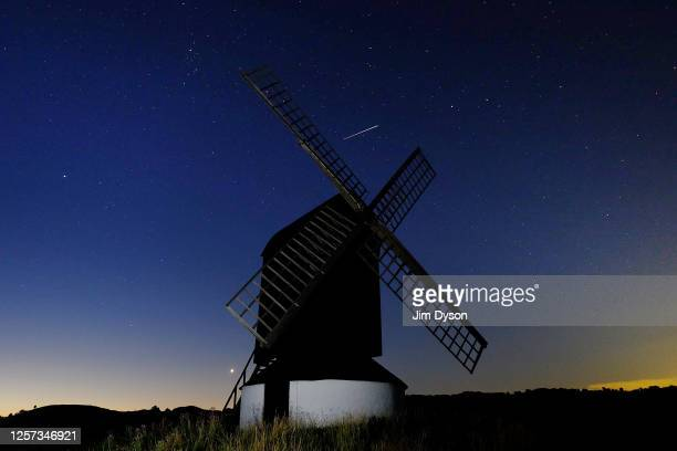 A meteor is seen in the sky behind Pitstone Windmill on July 20 2020 in Ivinghoe United Kingdom Pitstone Windmill is a gradeII listed post mill...
