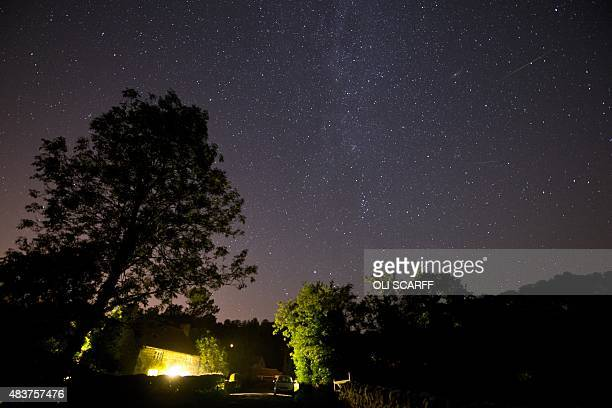 A meteor passes across the sky during the peak in activity of the annual Perseids meteor shower in the village of Rievaulx near Helmsley northern...
