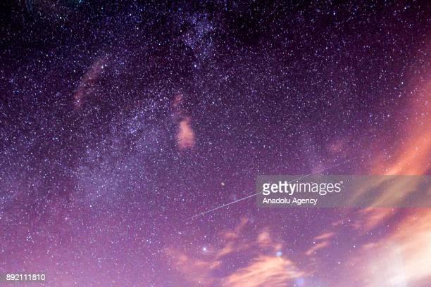 A meteor streaks across the night sky during the Geminid meteor shower over Turkey's Van on December 13 2017 'Geminid' Meteor Shower or 'Shooting...