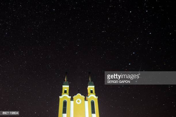 Meteor streaks across the sky behind a Catholic church during the annual Geminid meteor shower in the village of Krevo, some 100 km northwest of...