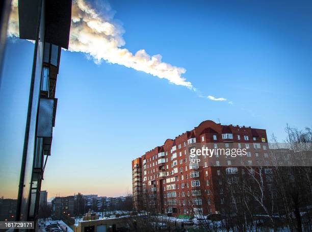 A meteorite trail is seen above a residential apartment block in the Urals city of Chelyabinsk on February 15 2013 A heavy meteor shower rained down...