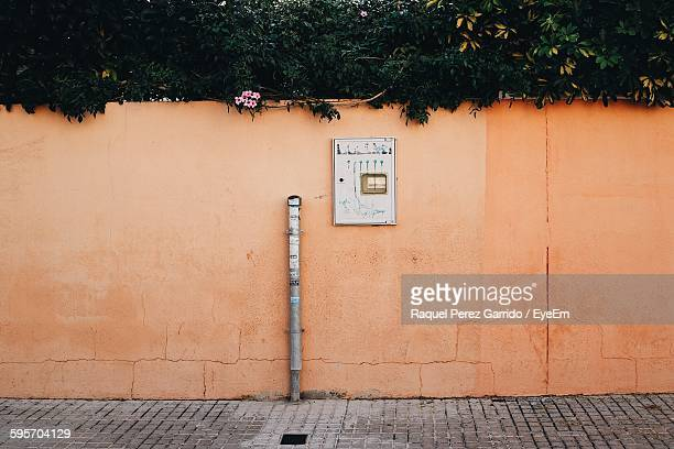 meter box on orange wall against trees - electrical box stock pictures, royalty-free photos & images