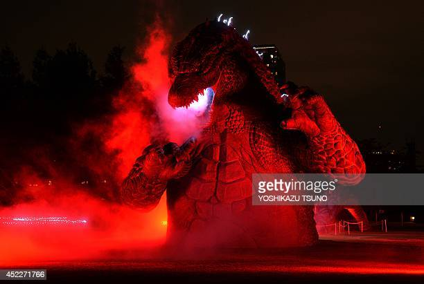 A 66 meter tall godzilla statue is illuminated at the Midtown park in Tokyo for the promotion of the recent godzilla movie at a press preview on July...