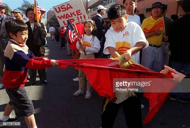 METetFlagRH––021399––A trio of kids pull apart a Communist flag during a protest at the strip mall where Truong Van Tran's now infamous video store...