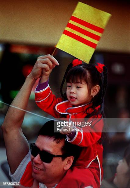 METetGirlRH––021399––Lan–Anh Ngo 3 1/2 yrs is all smiles as she waves a flag and sits on her dad's shoulders as they watch protesters parade through...