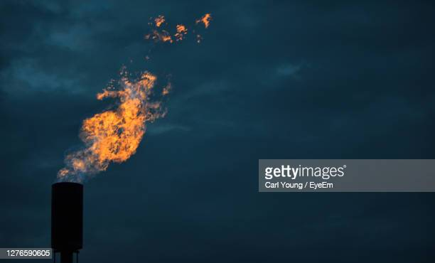 a methane flare burns against a twilight sky - illinois stock pictures, royalty-free photos & images