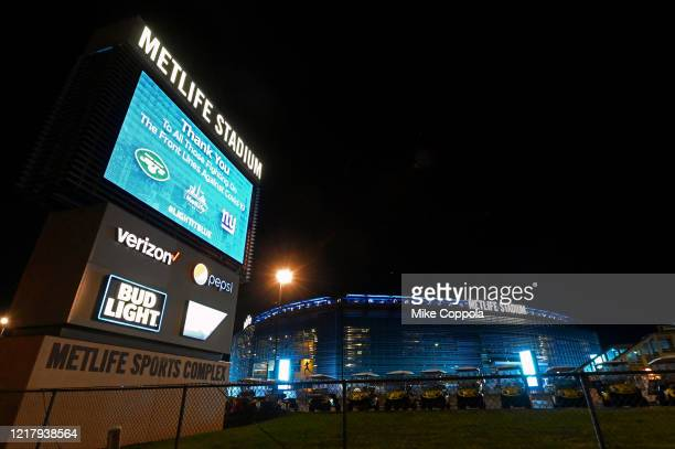 Metlife Stadium is illuminated in blue to honor essential workers on April 09, 2020 in East Rutherford, New Jersey. Landmarks and buildings across...