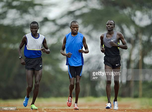 IAAF 5000 metres gold medalist Edwin Soi warms up during a training session with compatriot Thomas Longosiwa and an unidentified teammate on July 13...