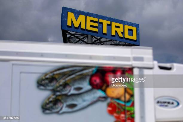 A Metro AG logo sits on a sign beyond a delivery truck outside the company's wholesale food distribution depot in Weiterstadt Germany on Wednesday...