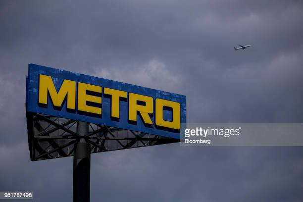 A Metro AG logo sits on a sign outside the company's wholesale food distribution depot as a Deutsche Lufthansa AG passenger plane flies beyond in...