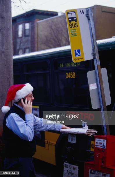 Metro bus driver, wearing Santa Claus hat and talking on mobile phone.