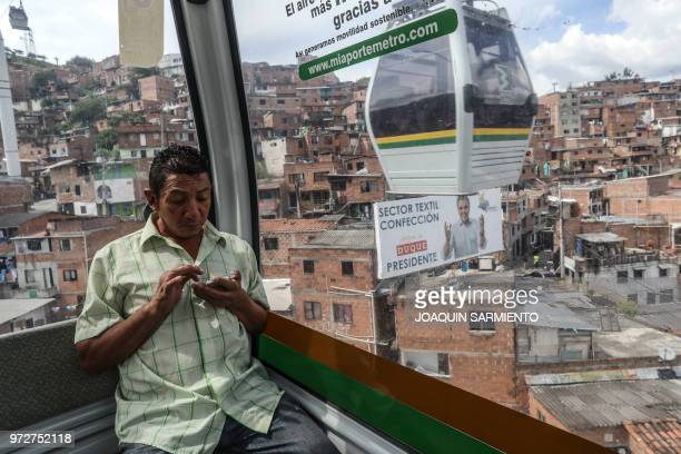 A metro cable car passes next to political advertising of Colombian presidential candidate Ivan Duque of the Centro Democratico party in Medellin...