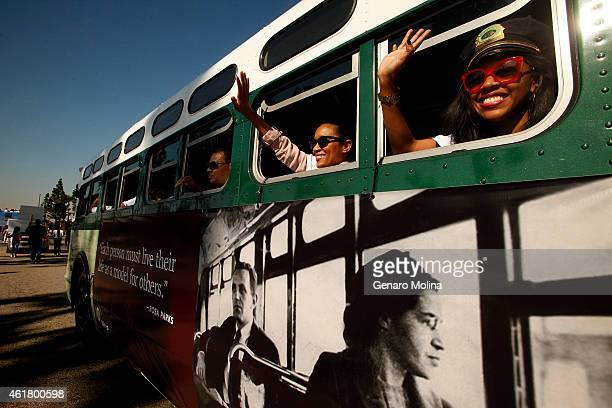 Metro employees Kinya Claiborne right and Shalonda Baldwin wave to the crowds from a Metro bus that is a replica of the bus that Rosa Parks was...