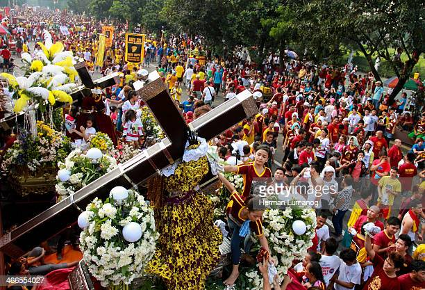 Metro Manila, Philippines-January 9, 2014: A young girl help people to have their towel wipe the face of replica statue of the Black Nazarene....