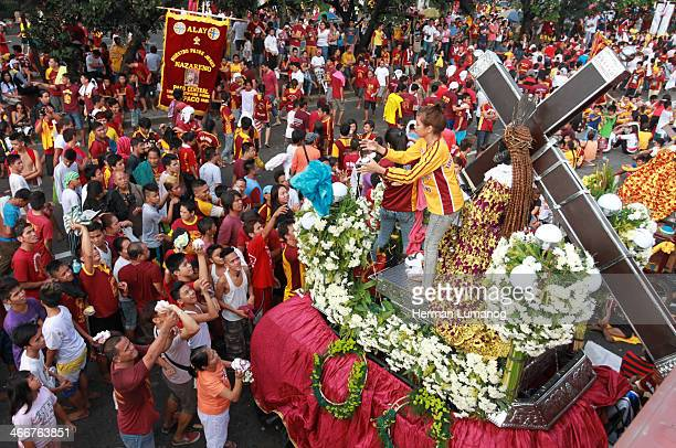 CONTENT] Metro Manila PhilippinesJanuary 9 2014 A young girl help people to have their towel wipe the face of replica statue of the Black Nazarene...