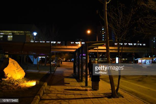 A metro passes by as a woman stands next to a bus station in Ankara Turkey on late January 4 2019