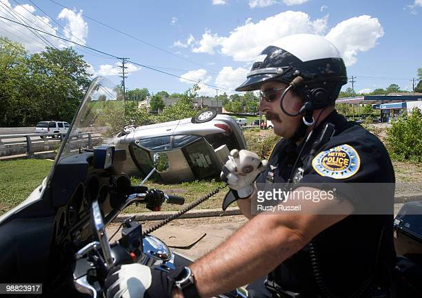 Metro Police Officer Jeff Porter talks with emergency crews at the scene of a destroyed automobile May 3 2010 in Nashville Tennessee More than 13...