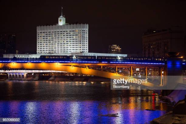 A metro train passes on a bridge over the Moskva River in front of the Russian White House government building in Moscow Russia on Wednesday March 14...