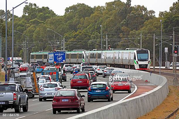 Metro train running down the middle of a congested freeway