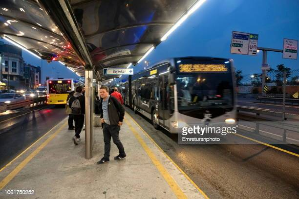 a metrobus public transport station with passengers and buses at sunset in istanbul. - emreturanphoto stock pictures, royalty-free photos & images