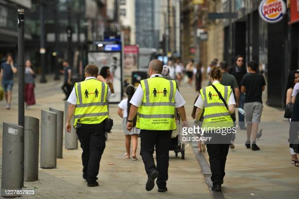 Metrolink workers wear high vis jackets with that urge social distancing as a precuation against the transmission of the novel coronavirus in...