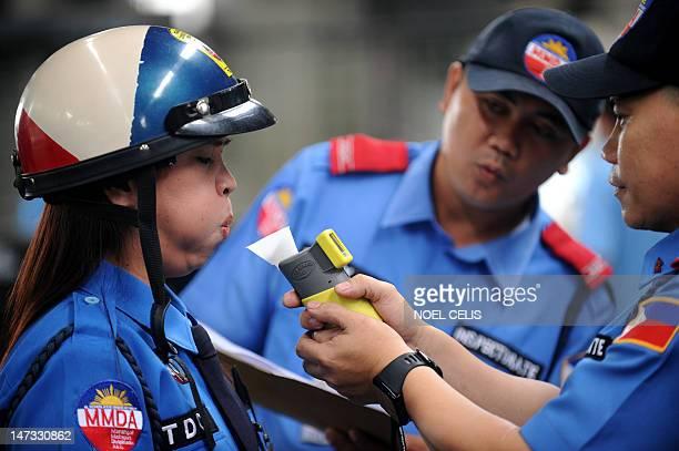 Metropolitan Manila Development Authority traffic aide Jenny Suzara undergoes a breathalyser test at an MMDA Traffic Emergency Station in Manila on...