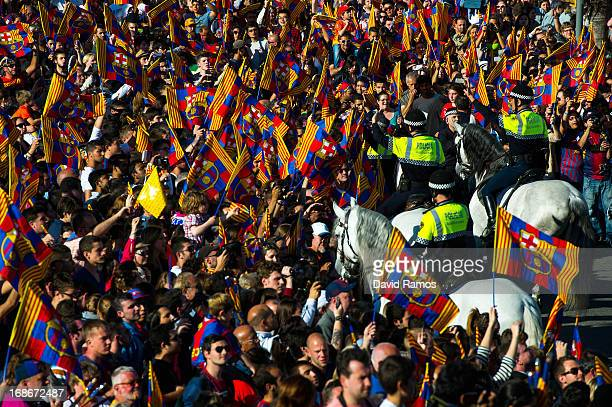 Metropolitan mounted police officers clear the way for the FC Barcelona open top bus during celebrations after winning the Spanish Liga on May 13...