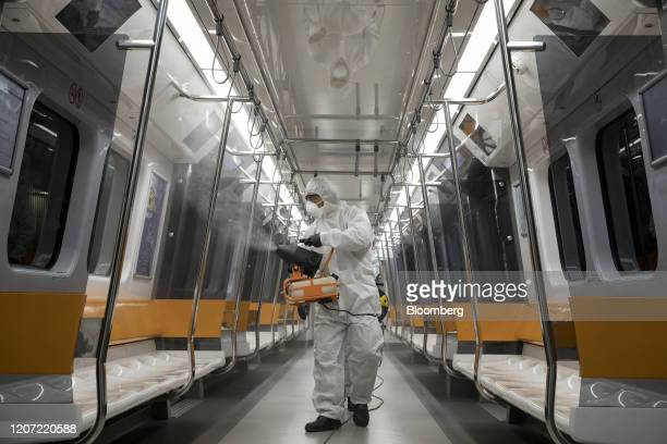 Metropolitan municipality workers wearing a hazmat suits spray disinfectant into a metro train in Istanbul Turkey on Saturday March 14 2020 Turkey...