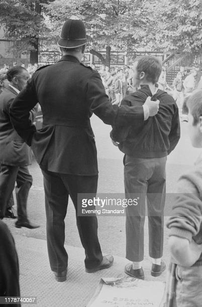 Metropolitan Police constable grips the harrington jacket of a skinhead youth during a street disturbance in Fulham Road, London on 7th September...