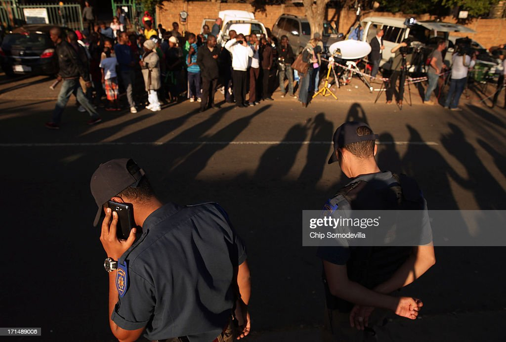 Metropolitan Police keep order as people line the street outside of the Mediclinic Heart Hospital where former South African President Nelson Mandela is being treated June 25, 2013 in Pretoria, South Africa. South African President Jacob Zuma confirmed on June 23 that Mandela's condition has become critical since he was admitted to the hospital over two weeks ago for a recurring lung infection.