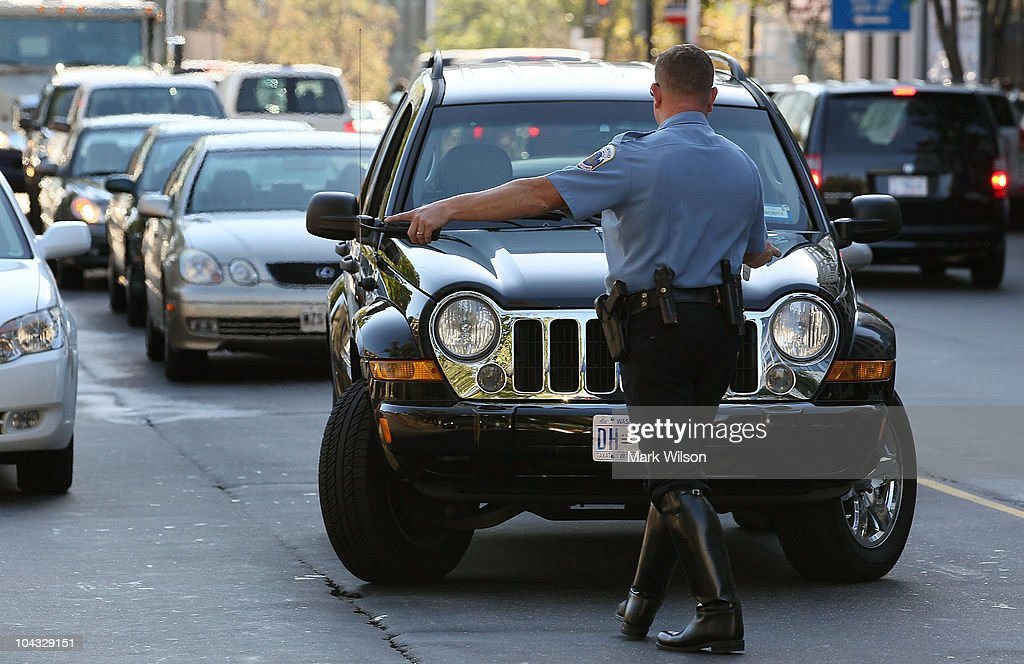 Metropolitan Police Officer J.D. Hansohn, flags down a driver who was talking on his cell phone on September 21, 2010 in Washington, DC. Police were giving warnings and tickets to people who were talking on cell phones while driving past a hotel where the 2010 Distracted Driving Summit was being held.