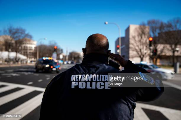 Metropolitan Police officer salutes as a hearse carrying the casket of Brian Sicknick, U.S. Capitol Police Officer who died from injuries following...