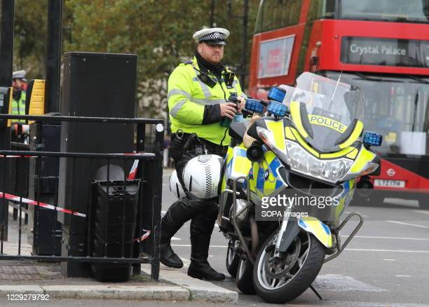 Metropolitan Police officer seen next to his police motorcycle at the end of Whitehall ready to stop traffic on entrance to Westminster. With a...