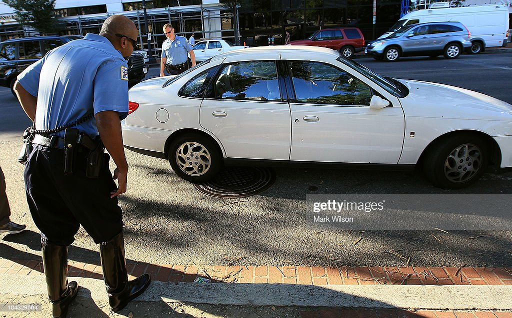Metropolitan Police Officer Tyrone Gross (L) and Officer J.D. Hansohn (R) flag down a motorist who were talking on her cell phone on September 21, 2010 in Washington, DC. Police were giving warnings and tickets to people who were talking on cell phones while driving past a hotel where the 2010 Distracted Driving Summit was being held.