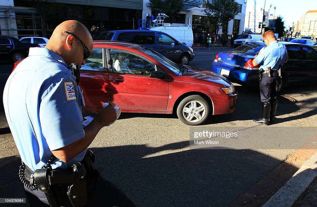 Metropolitan Police Officer Tyrone Gross (L) and Officer J.D. Hansohn (R) write warning tickets to motorists who were talking on their cell phones on September 21, 2010 in Washington, DC. Police were giving warnings and tickets to people who were talking on cell phones while driving past a hotel where the 2010 Distracted Driving Summit was being held.