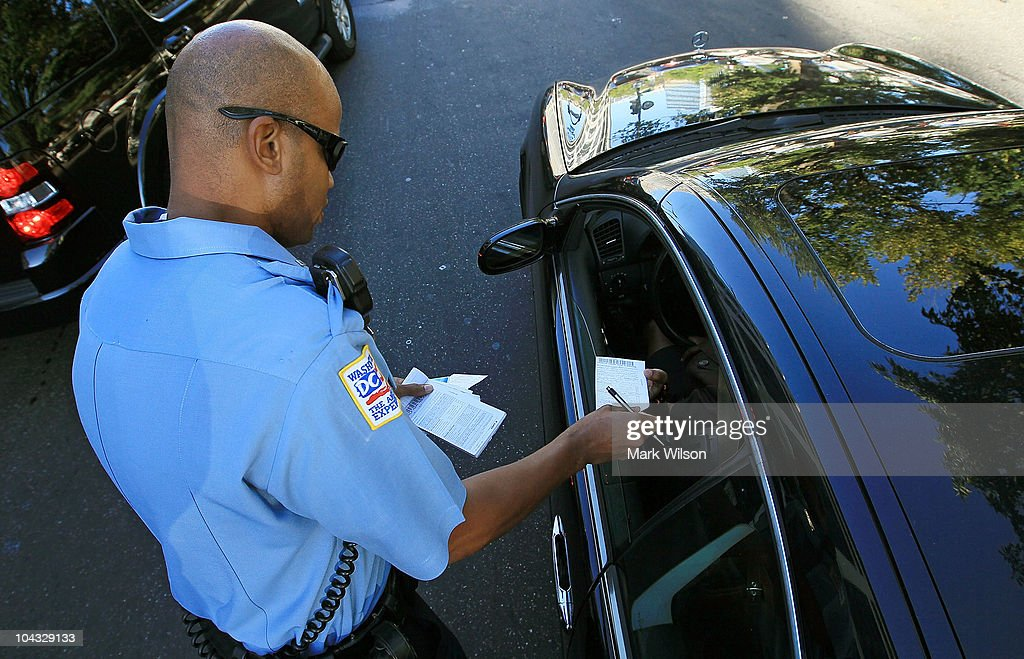 Metropolitan Police Officer Tyrone Gross, hands out a warning to motorist who was talking on his cell phone on September 21, 2010 in Washington, DC. Police were giving warnings and tickets to people who were talking on cell phones while driving past a hotel where the 2010 Distracted Driving Summit was being held.