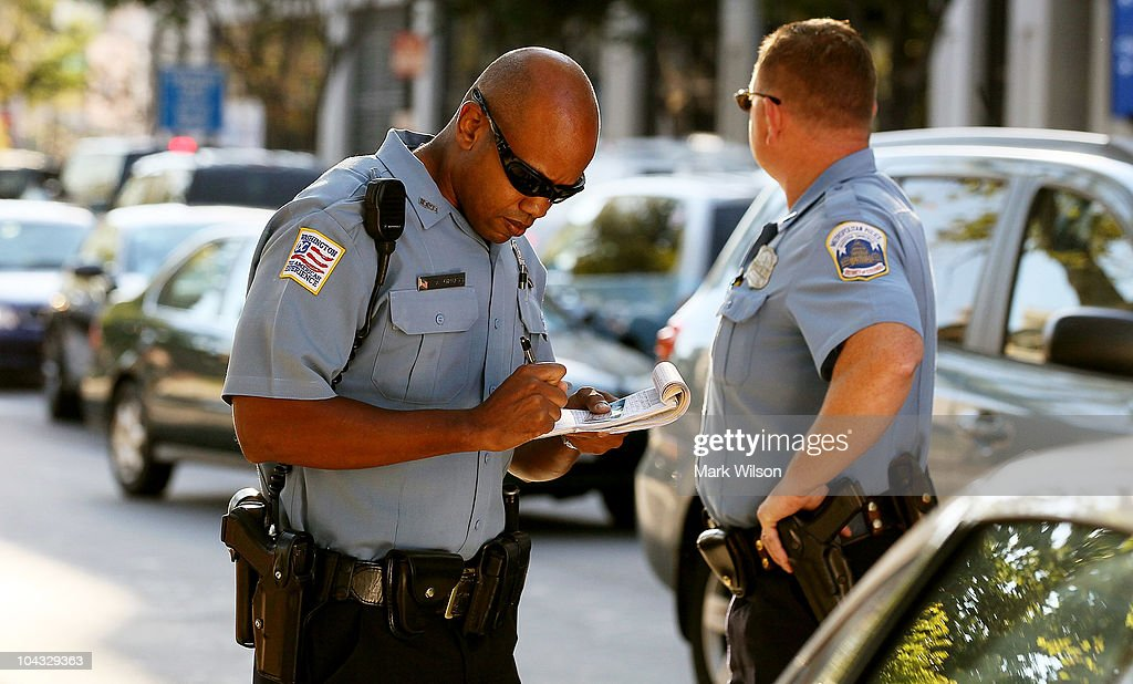 Metropolitan Police Officer Tyrone Gross (L) writes a warning ticket to a motorist who was talking on her cell phone while Officer J.D. Hansohn (R) looks for other offenders on September 21, 2010 in Washington, DC. Police were giving warnings and tickets to people who were talking on cell phones while driving past a hotel where the 2010 Distracted Driving Summit was being held.