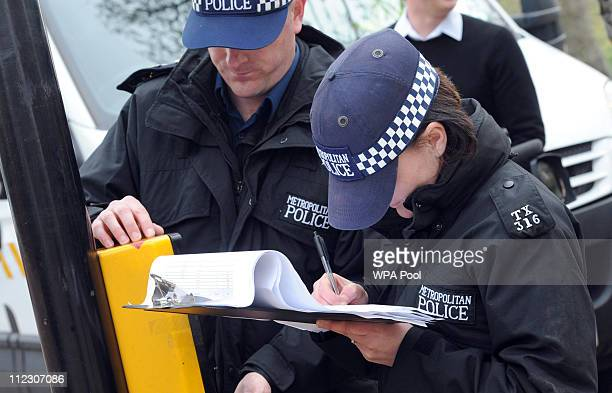 Metropolitan Police officers carry out security checks on drains and lamp posts along the Mall ahead of the forthcoming Royal wedding on April 14...