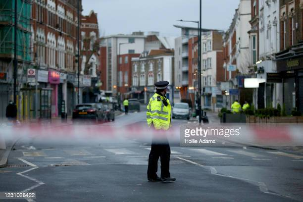 Metropolitan Police officers standing behind a police cordon at the scene of a stabbing at Willesden Lane on February 7, 2021 in London, England....